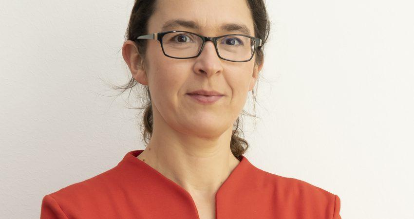 Portrait von Claudia Maicher in roter Bluse vor weißer Wand