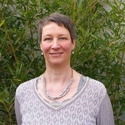 Portrait von Claudia Kurzweg vor grünem Busch
