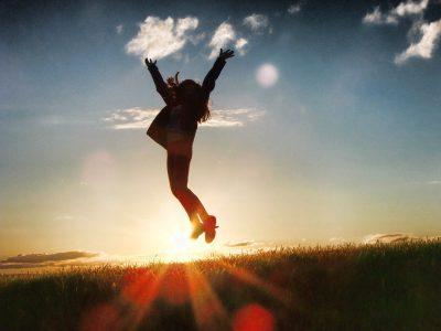Kind springt freudig in die Höhe vor Getreidefeld im Sonnenuntergang © Shad0wfall / pixabay