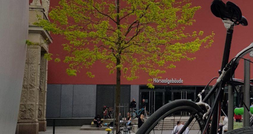 Angelehnte Fahrräder mit Hoorsaalgebäude am Campus Augustusplatz (Uni Leipzig) im Hintergrund