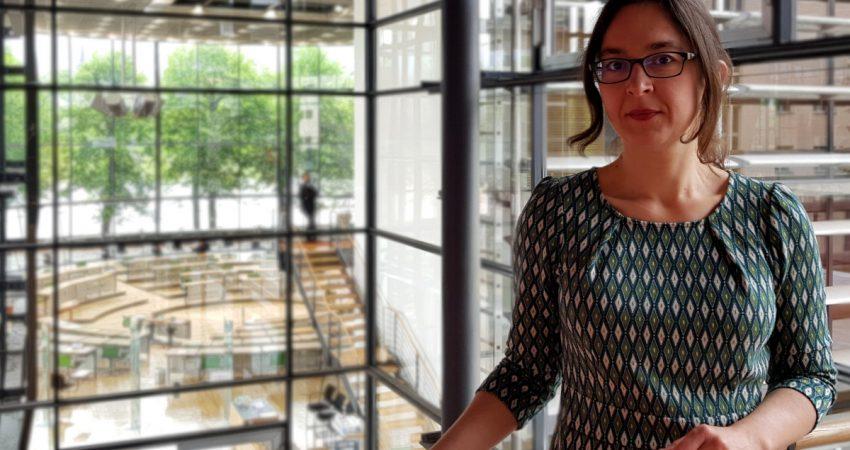 Claudia Maicher im Landtag mit Plenarsaal im Hintergrund